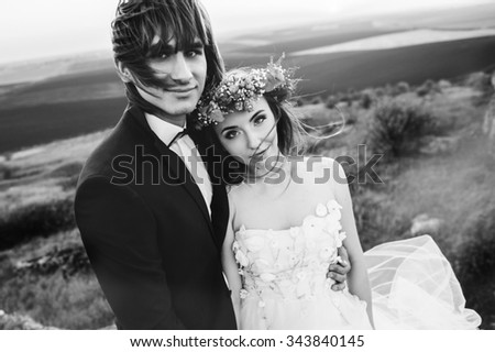 beautiful stylish groom holding fabulous happy emotional bride on the background of the sunny stunning mountains