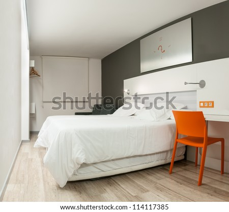 Beautiful stylish interior in modern style. Elegant design of furniture. Clean empty hotel room with double bed. Contrast of pastel colors and bright details. Night with closed window and light on. - stock photo
