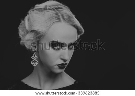 Beautiful stylish model in black dress on a dark background. Beautiful makeup. Stylish dress and jewelry. Photo for fashion magazines, posters and websites.