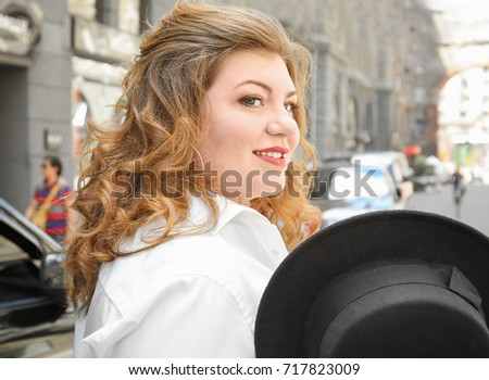 Beautiful stylish overweight woman with hat on street