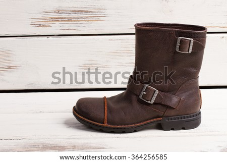 Beautiful stylish pair of men's winter boots with fur. Men's shoes on retro wooden background. - stock photo
