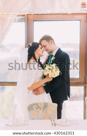 Beautiful stylish pair of newlyweds embracing each other in luxurious restaurant interior. Bright window as background