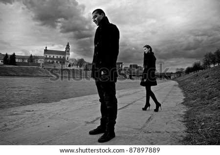 Beautiful stylish pair of young people outdoor going in different directions. - stock photo