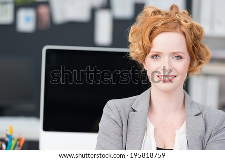 Beautiful stylish redhead businesswoman posing in the office facing the camera with a lovely smile - stock photo