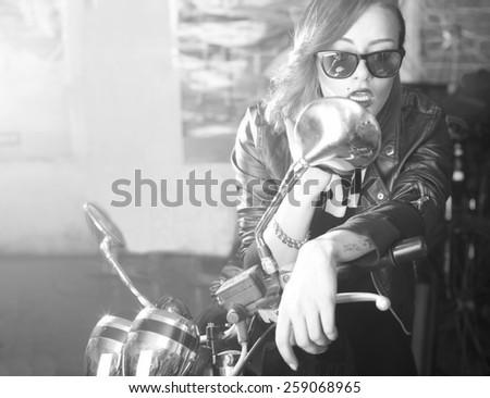 Beautiful stylish woman posing with motorcycle. - stock photo