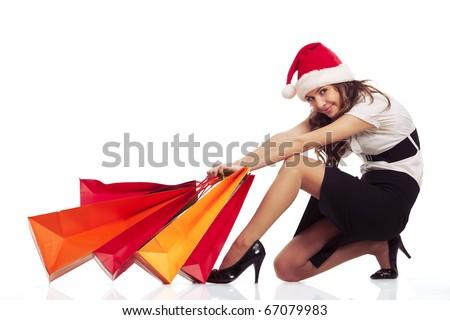 Beautiful stylish woman pulling christmas shopping bags - stock photo