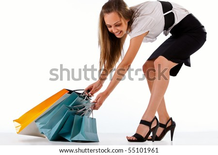 Beautiful stylish woman pulling shopping bags - stock photo