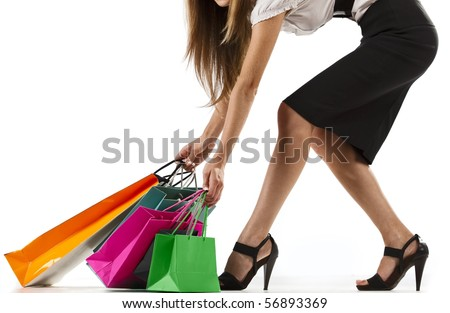 Beautiful stylish woman pulling shopping bags - stock photo