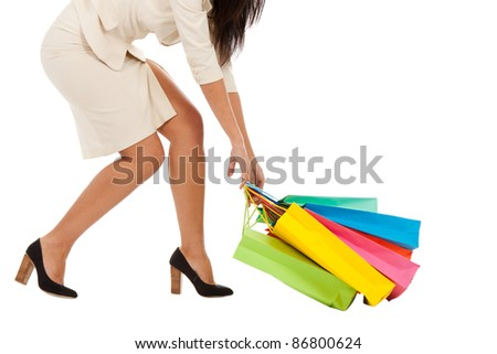 Beautiful stylish woman pulling shopping bags, legs in high heels. Isolated on white background