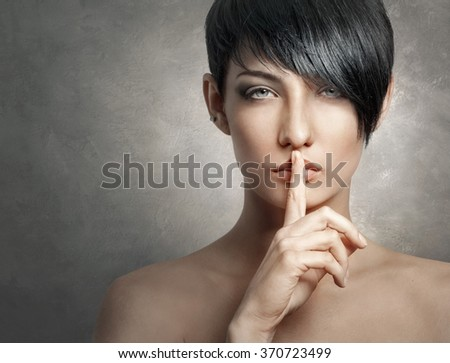 Beautiful stylish woman showing gesture holding her finger to her lips for silence or secrecy    - stock photo