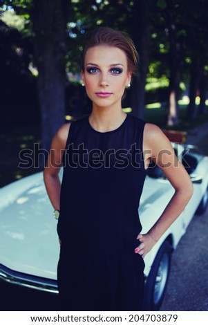 Beautiful stylish woman standing on background of her luxury classic cabriolet car and looking at the camera, lifestyle and successful business concept - stock photo