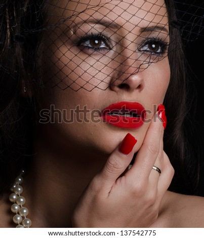 Beautiful, stylish woman with bright red lips and nails, wearing a hat while staring intently.