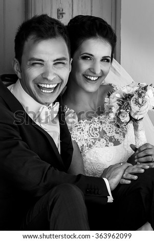 Beautiful stylish young bride and groom near the door of the church embracing and kissing