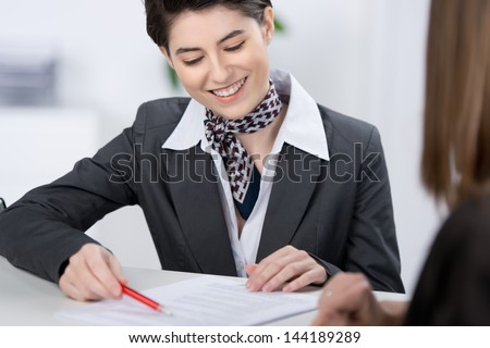 Beautiful stylish young customer services representative explaining a document to a customer with a lovely friendly smile - stock photo
