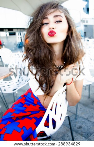 Beautiful stylish young fashion girl with perfect evening make-up with pink lips and green eyes in elegant clothes hills,skirt,top and jacket dress catalogue summer collection,street cafe,send kiss - stock photo