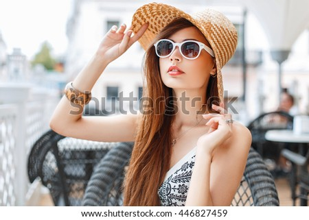 Beautiful stylish young girl in a straw hat and sunglasses sitting in a cafe on a sunny day