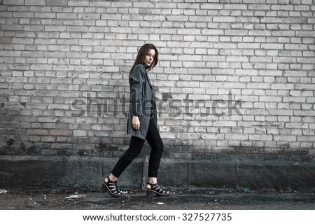 Beautiful stylish young girl in fashionable gray coat posing on brick wall background