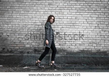 Beautiful stylish young girl in fashionable gray coat posing on brick wall background - stock photo