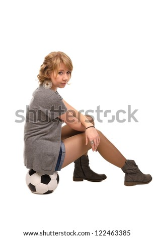 Beautiful stylish young girl with curly blonde hair sitting on a soccer ball looking over her shoulder at the camera isolated on white - stock photo