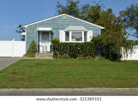Beautiful Suburban Blue Bungalow Home Sunny Clear Blue Sky Day residential neighborhood USA - stock photo