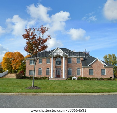 Beautiful Suburban Brick Brownstone McMansion home Autumn Fall Day residential neighborhood USA blue sky clouds