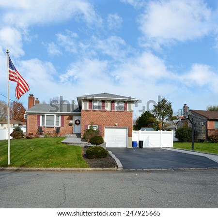 Beautiful Suburban Brick Snout style home landscaped yard residential neighborhood USA blue sky clouds - stock photo