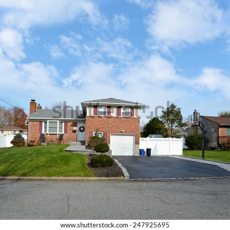 Beautiful Suburban Brick Snout style home landscaped yard residential neighborhood USA blue sky clouds