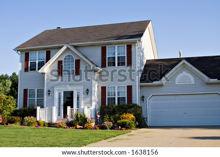 Beautiful suburban family home in summer - flowers decorate yard. - stock photo