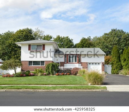 Beautiful Suburban High Ranch Home Sunny Residential Neighborhood Blue Sky Clouds USA - stock photo