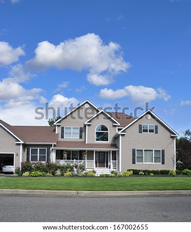 Beautiful Suburban McMansion Home Landscaped Lawn Flowers Plants Residential Neighborhood USA Blue Sky Clouds - stock photo