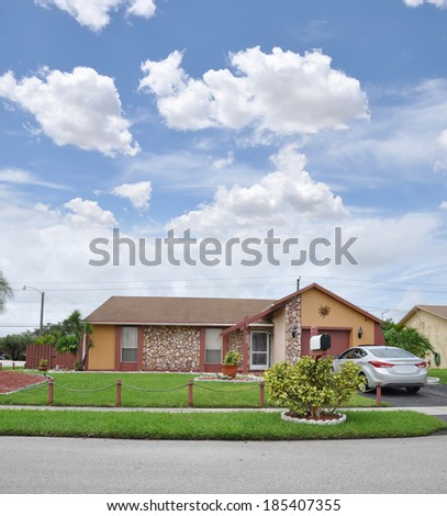 Beautiful Suburban Ranch Style Brownstone Home Landscaped residential neighborhood usa blue sky clouds - stock photo