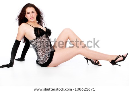 Beautiful sultry sexy young brunette woman wearing black lingerie nightie, gloves and high heels posing for the camera - stock photo