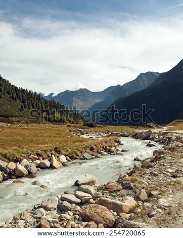 Beautiful summer Alpine mountain river view and sunshine in sky - stock photo