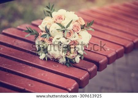 Beautiful summer bridal bouquet lying on a park bench, wedding day, celebration - stock photo
