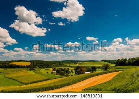 Beautiful summer clouds over rolling hills and farm fields in rural York County, Pennsylvania. - stock photo