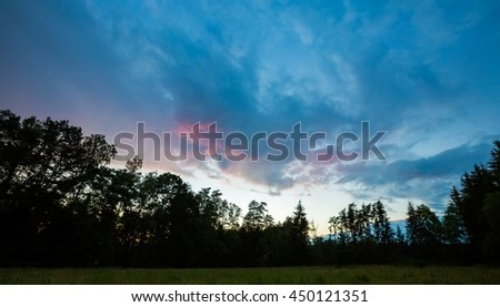 Beautiful summer colorful sunset over green meadow and forest. Vibrant polish landscape - stock photo
