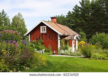 Beautiful summer cottage with flower in the garden. - stock photo