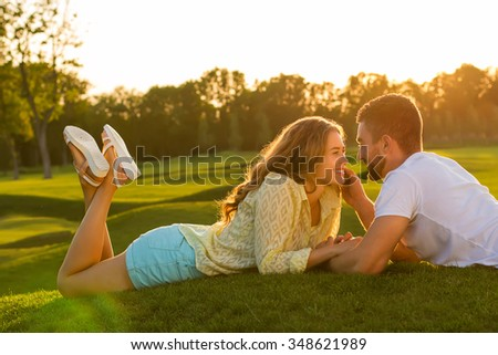 Beautiful summer evening. Loving couple lying on the grass. Happy people. - stock photo