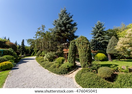 Beautiful summer garden design, with conifer trees, green grass and morning sun. Professional luxury gardening concept. Garden road with guidepost
