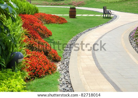Beautiful summer garden with a walkway winding its way through - stock photo