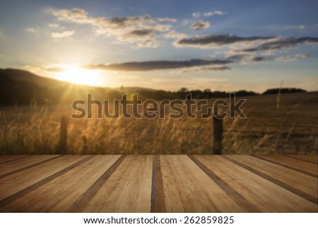 Beautiful Summer image of sun shining and backlighting countryside landscape with wooden planks floor - stock photo