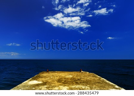 Beautiful summer landscape - concrete pier on the background of the dark blue sea on a sunny day, Crimea - stock photo