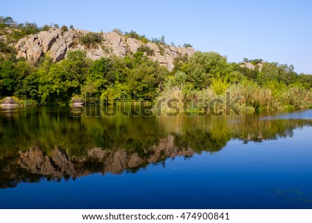 Beautiful summer landscape. Forest calm river with mountain rock and water mirror. Amazing nature background with clear lake and forest. and forest. Tourism, peace, relaxation, travel.