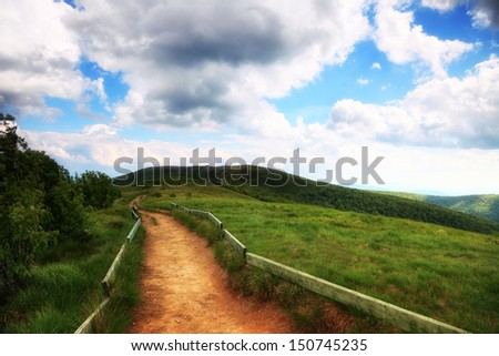 Beautiful summer landscape in the mountains. Pathway through the grassy hills, dark sky with clouds Bieszczady Poland