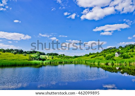 Beautiful summer landscape on the lake, the lake green grass and blue sky. The reflection of the sky in the water