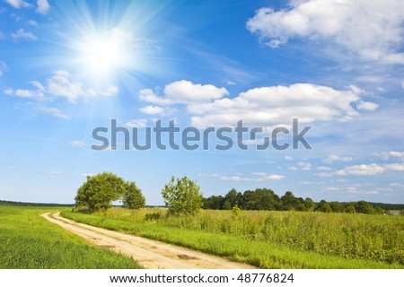 Beautiful summer landscape with a country road and white clouds in the blue sky - stock photo