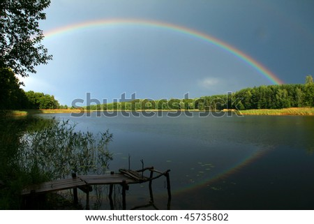 beautiful summer  landscape with rainbow above the lake - stock photo