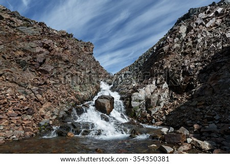 Beautiful summer mountain landscape: picturesque view of the mountain river into steep cliffs on a background of blue sky with clouds on a sunny day. Eurasia, Russia, Far East, Kamchatka Peninsula. - stock photo