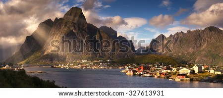 Beautiful summer panorama of Reine village, Norway, Lofoten Islands, with mountains, fjord, clouds and sunshine. - stock photo