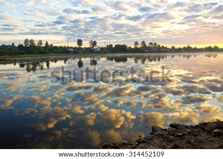 Beautiful summer sunrise with multicolored sky reflection in river